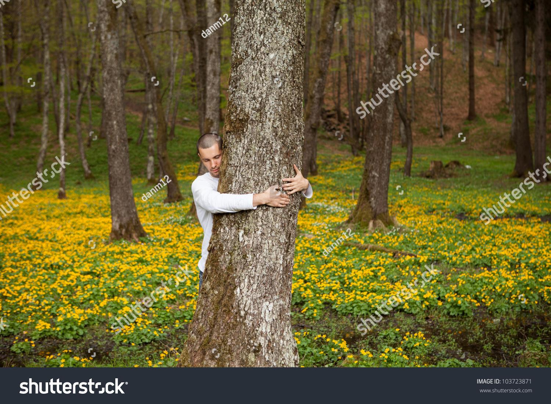 一个快乐的人拥抱一棵树在森林-自然,宗教-海洛创意()