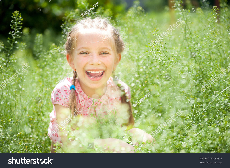 可爱的微笑的小女孩在草地上在阳光明媚的一天