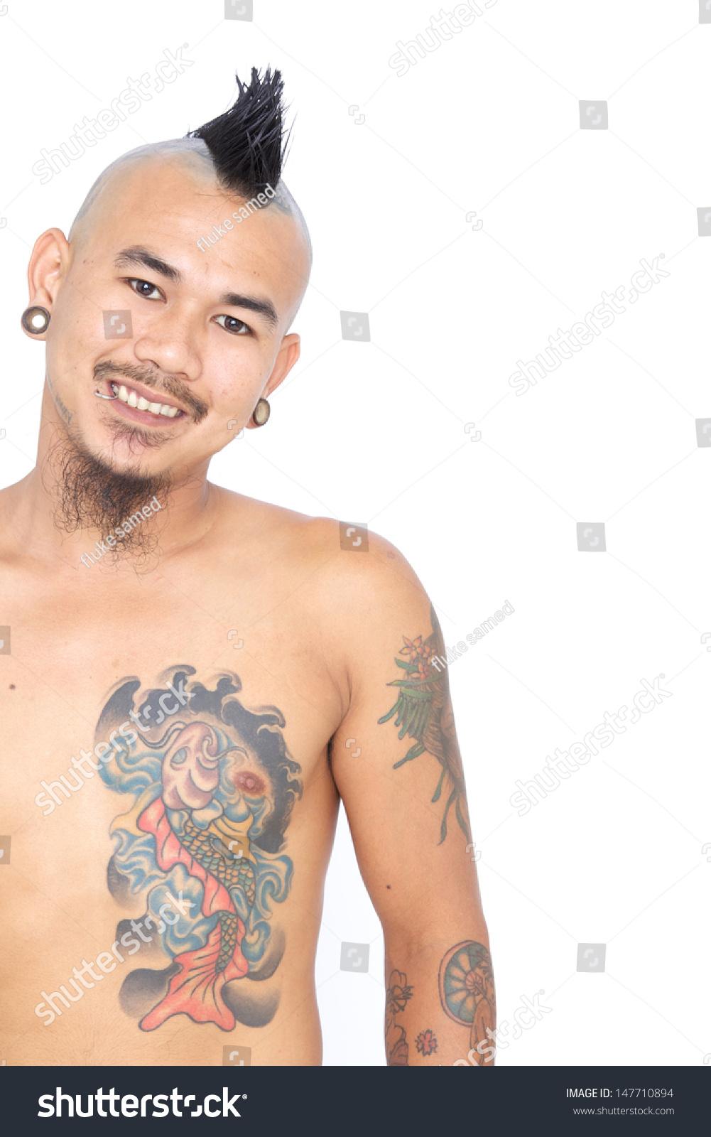 微笑的画像亚洲朋克人莫霍克发型,穿刺和纹身孤立在的