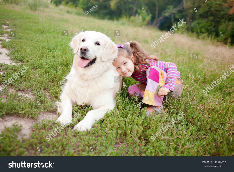 快乐的孩子和狗品种的金毛寻回犬在绿草在公园里.