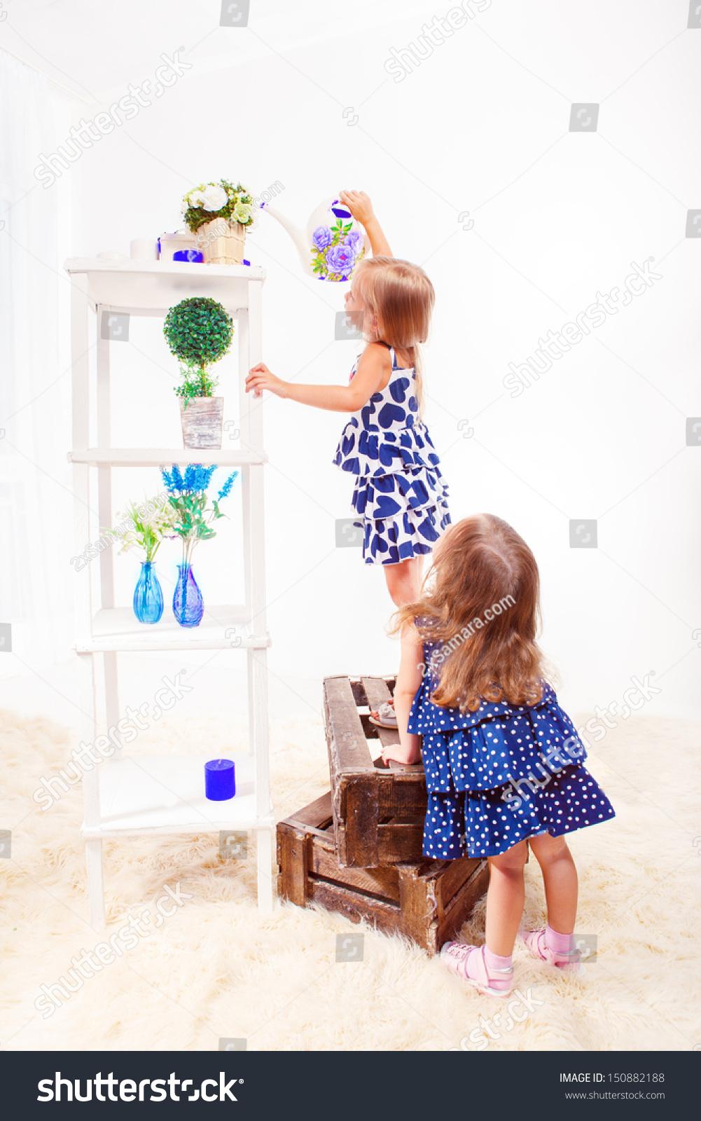 两个可爱的小女孩在客厅给花浇水