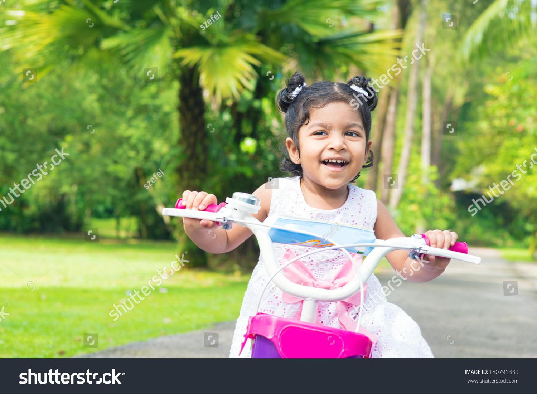 可爱的印度女孩骑自行车户外花园.孩子玩的自行车.