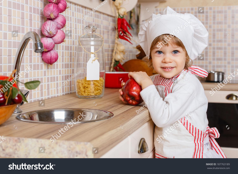 小女孩在围裙和帽子的厨师一个苹果站在家里的厨房.的