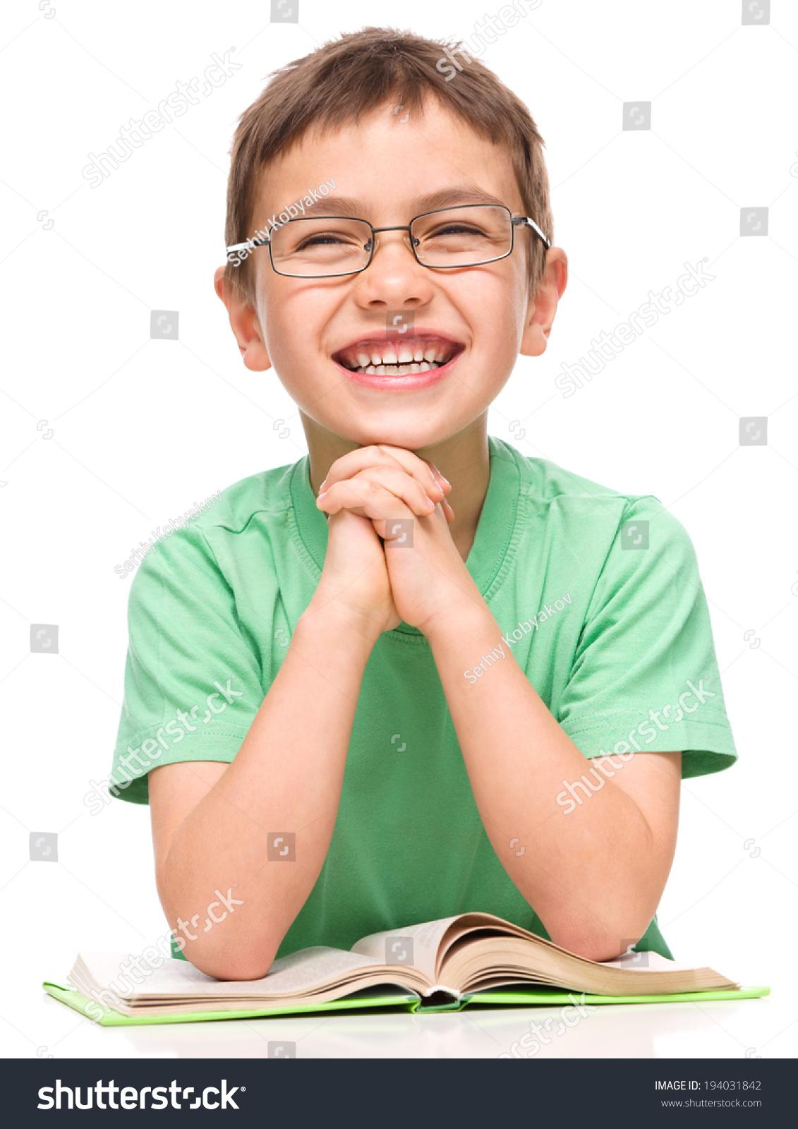 可爱的小男孩正在读一本书时戴眼镜