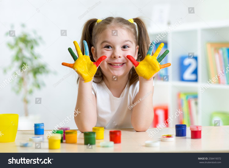 可爱的小孩的女孩用手画彩色的颜料在托儿所