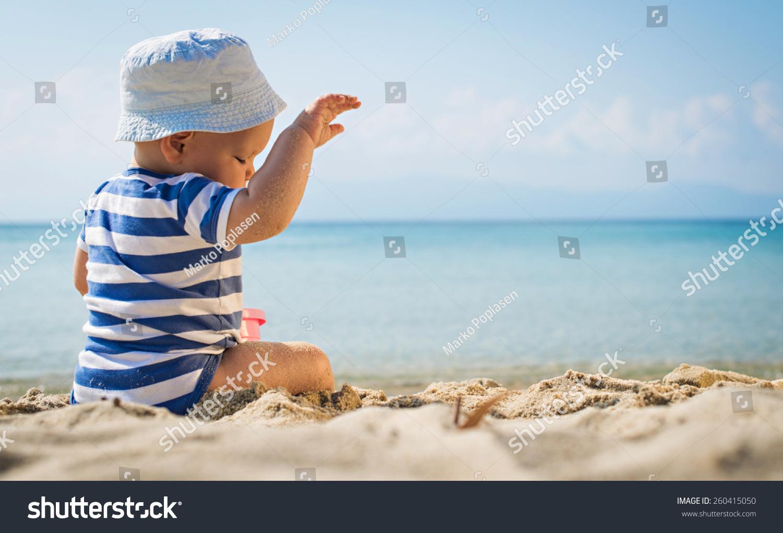 可爱的小男孩在海滩上玩.小男孩坐在沙滩上.海洋和.