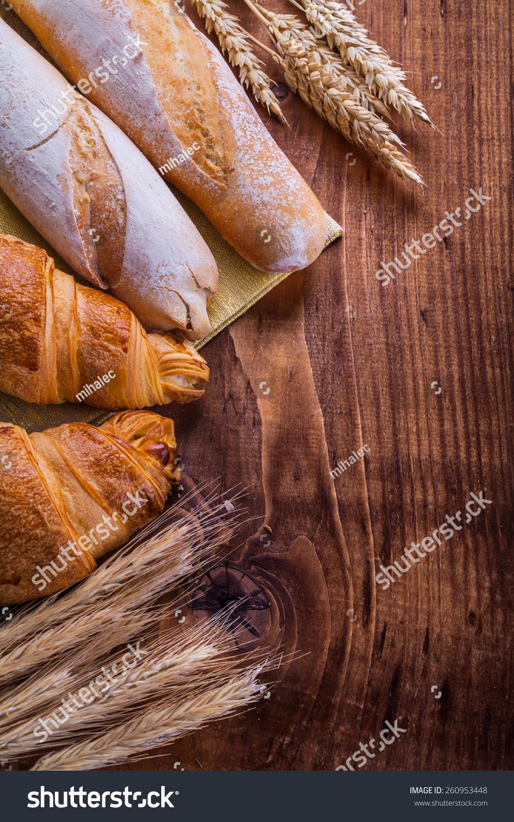 面包小麦和耳朵上的木板食品和饮料的概念