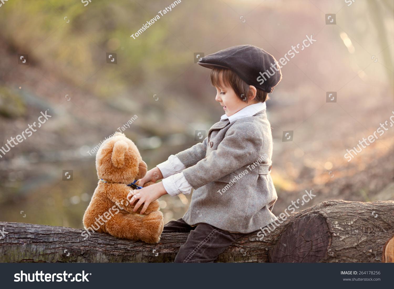 可爱的小男孩在公园和他的泰迪熊朋友在日落,漂亮的光