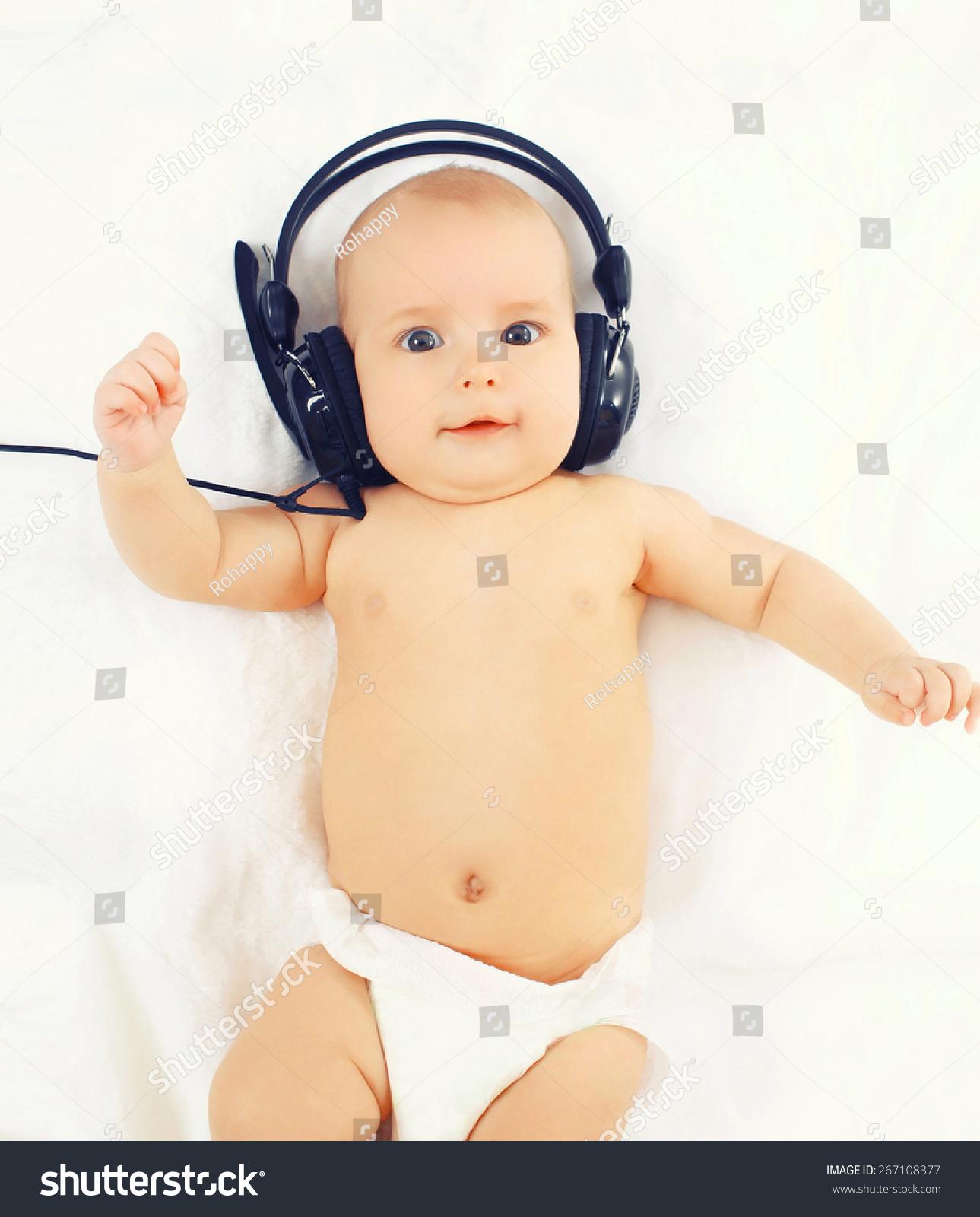 可爱的宝宝的画像在耳机躺在床上听音乐
