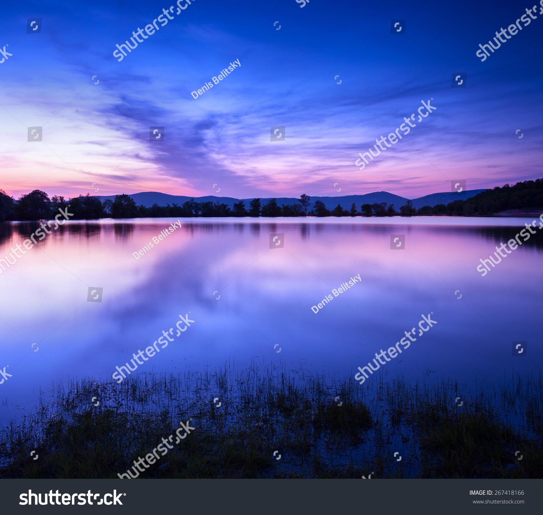 美丽的春天的夜晚,在池塘里有星星,云朵和倒影在-自然