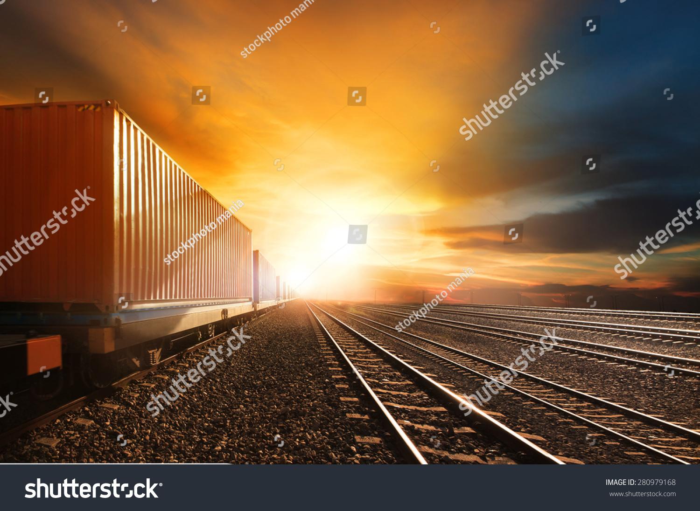 行业集装箱列车运行在铁路轨道对美丽的日落天空使用土地运输和物流