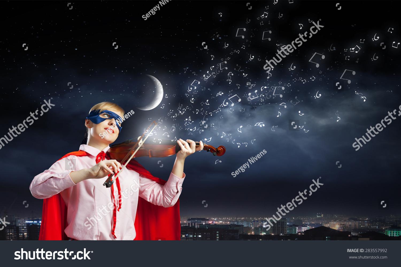 年轻女子在超级英雄服装演奏小提琴图片