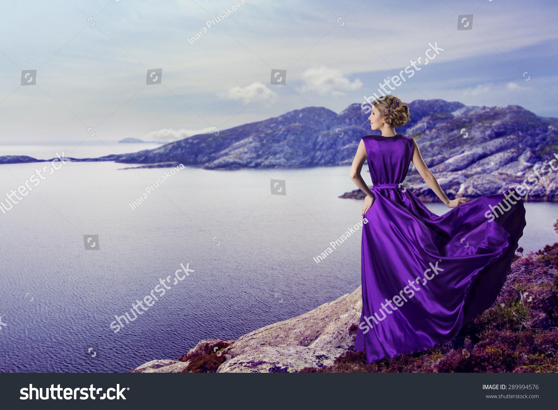 女人穿着紫色的高山大海,挥舞着礼服飞在风,优雅的