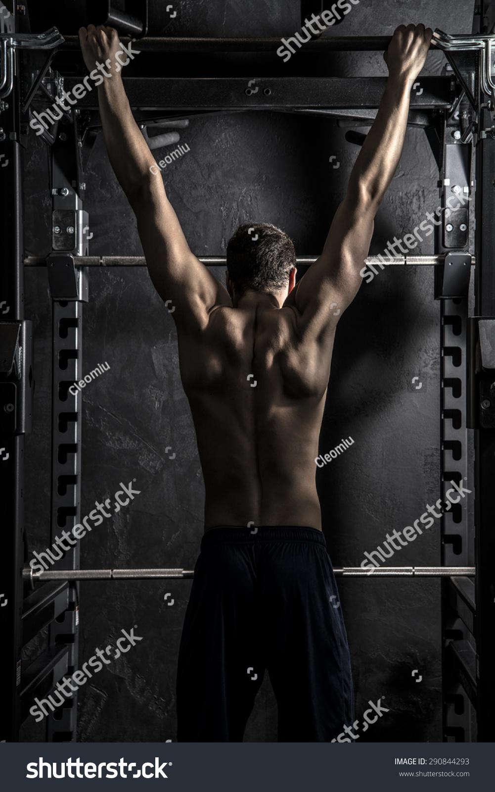 健身,年轻运动员强壮的男人展示从背部肌肉健身酒吧