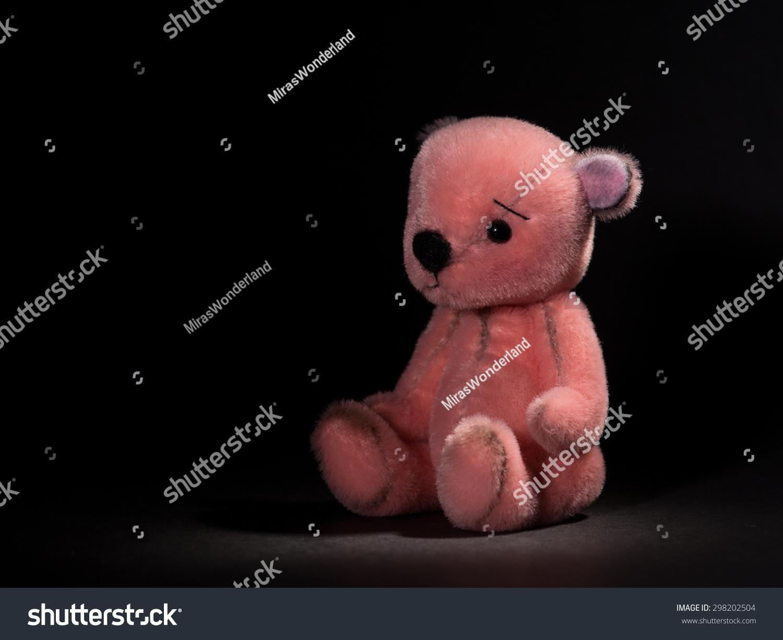 可爱的小粉红泰迪熊毛绒动物在一个黑色的背景-物体